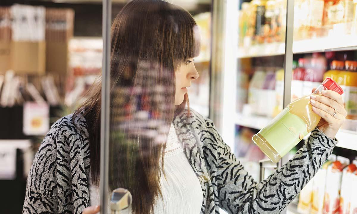 En tjej läser på baksidan av en juiceförpackning