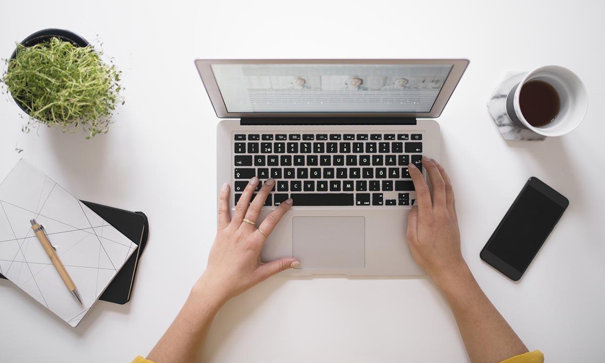 Händer skriver på en dator som står på ett bord.