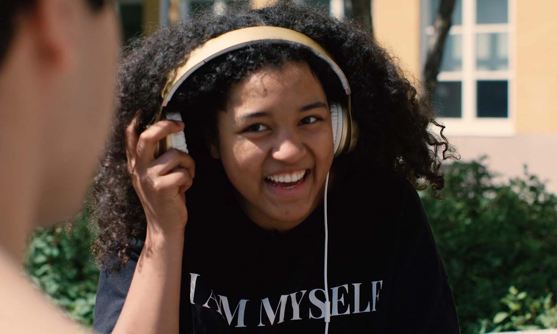 Glad tjej lyssnar på musik i hörlurar från filmen Shoppa smart!